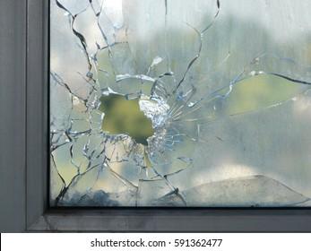 戦争射撃中に発砲された弾丸によって窓ガラスの穴。穴の周りに広がる亀裂。ガラスのぼやけた木の緑の葉。汚れた窓枠。内側から通りを望む。