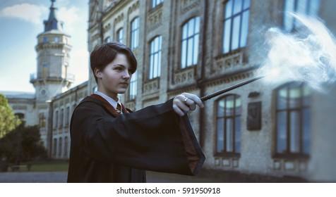 Mago, varita mágica, hechizo de lanzamiento de bruja al aire libre, de pie detrás del castillo