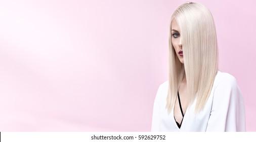 白いドレスの優雅なスタイリッシュな魅力的な女の子-ピンクの背景に