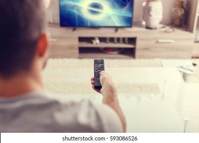 テレビで自宅でSFを見ているリモコンを持つ男