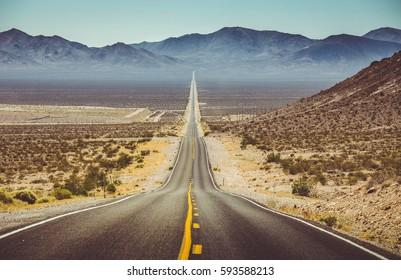 夏の青い空と美しい暑い晴れた日に極端な熱ヘイズでアメリカ南西部の不毛の風景を走る無限の直線道路の古典的な垂直パノラマビュー