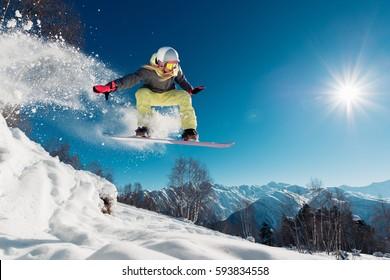 Niña salta con snowboard desde la colina
