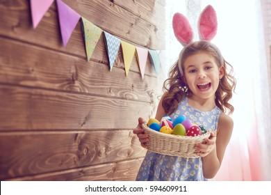 イースターの日にウサギの耳を着ているかわいい子供。塗られた卵のバスケットを持って女の子。