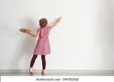 Nettes kleines Mädchen, das an der Wand im leeren Raum malt