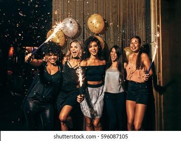 パブで大晦日を祝う若い女性のグループのショット。ナイトクラブでパーティーをする線香花火を持つ女性の友人のグループ。
