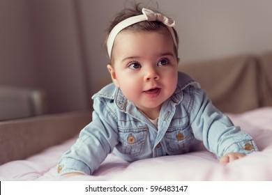 美しい女の赤ちゃんクロールとベッドで寝返り