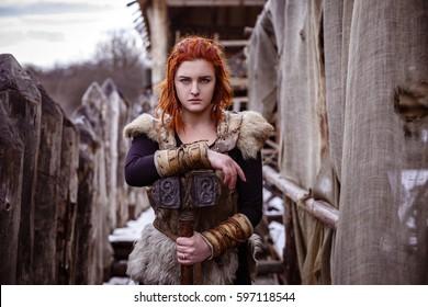 Wikingerfrau mit Hammer in traditioneller Kriegerkleidung. Vor dem Hintergrund eines großen Wikingerdorfes.