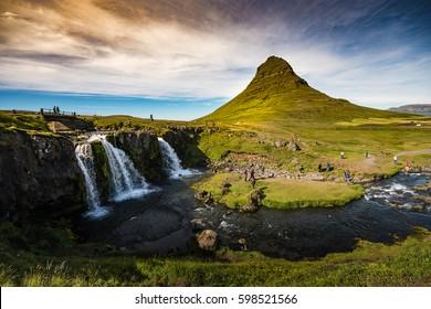 Kirkjufell & Kirkjufellfoss in Iceland with green mountain, waterfall and bright sky in summer.