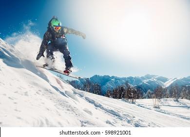 スノーボーダーがスノーヒルからスノーボードでジャンプしている