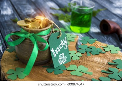 """Happy St Patrick's Day concept, Shiny Pot of Gold Leprechaun, clover trefoils, Greeting card with text """"Lucky"""",  tobacco pipe and green ale on wooden stump."""