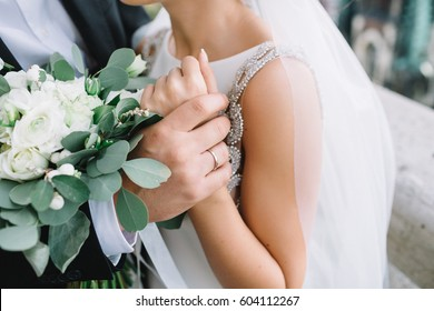 Close-up of groom's hand holding bride's wirst tender