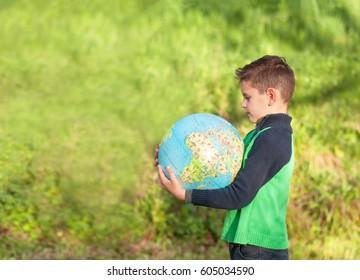 Chico guapo está sosteniendo un globo. Alumno en el parque, estudiando el mapa del mundo.
