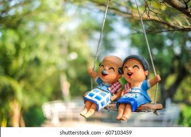 La pareja amante abuelo muñecas de arcilla sentado en columpios en el parque.