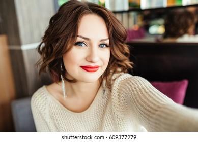 Selfie-retrato de linda chica morena con pelo corto sentado a la mesa en la terraza del restaurante. Viste un suéter amarillo y se ve feliz