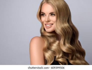 Blond meisje met lang en volume glanzend golvend haar. Mooi vrouwenmodel met krullend kapsel.