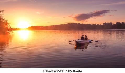 川に沈む夕日。恋人たちは美しい夕日の中に湖でボートに乗る。幸せなカップルの女と男が一緒に水でリラックス。周りの美しい自然。