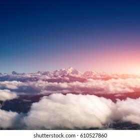 cielo y grandes montañas sobre nubes al atardecer o al amanecer. puesta de sol con una altura de 10000 km. Vista superior