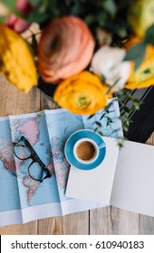 Beautiful yellow, white and pink ranunculus, fresh morning cup of espresso coffee with beautiful crema, notebook, glasses and a world map on the wooden table background: essentials for planning a trip