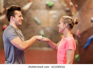 fitness, extreme sport, bouldering, people and healthy lifestyle concept - man and woman exercising at indoor climbing gym making fist bump gesture