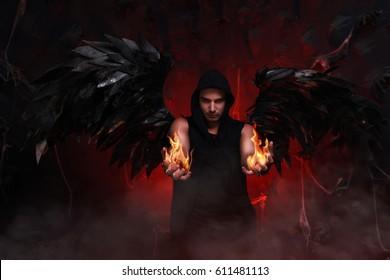 Hermoso hechicero con fuego en brazos y alas negras