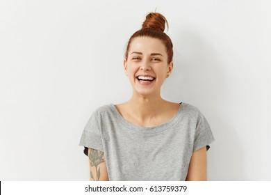 Feliz alegre joven vistiendo su pelo rojo en bollo regocijándose en noticias positivas o regalo de cumpleaños, mirando a la cámara con una sonrisa alegre y encantadora. Chica estudiante de jengibre relajante en el interior después de la universidad