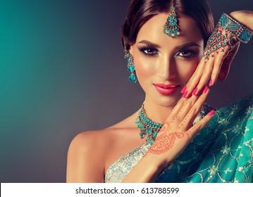 美しいインドの女の子の笑顔の肖像画。青い宝石セットを持つ若いインドの女性モデル。伝統的なインドの衣装サリー。