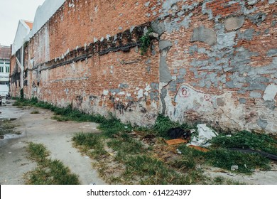 Red Brick Wall with Unfinished Wall Painted from The Street of George Town. Penang, Malaysia.