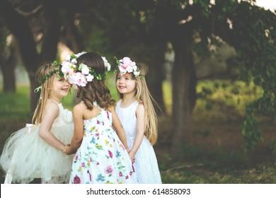 3人の愛らしい春の女の子が庭で一緒に遊ぶ