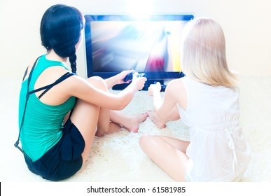 Two young women playing in computer games. Bright white colors.