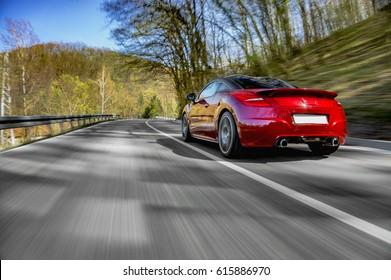 Generischer roter Sportwagen, der schnell auf offener Straße fährt