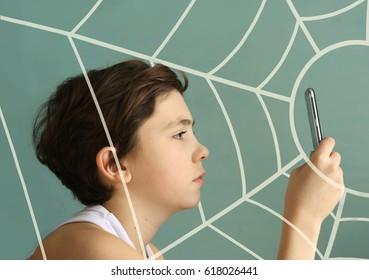 Computerspielsüchtiger Teenagerjunge Nahaufnahmefoto, das Telefon mit Spinnenspinnennetz als Symbol der Sucht spielt