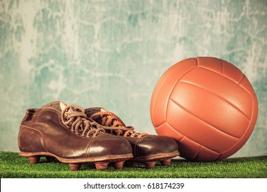 Retro outdated soccer spike boots and football. Vintage old style filtered photo