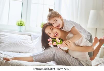 母の日おめでとう!子娘はお母さんを祝福し、花にチューリップとはがきを贈ります。ママと女の子の笑顔と抱擁。家族の休日と一体感。