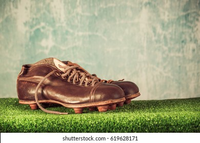 Retro outdated soccer or football spike boots. Vintage old style filtered photo