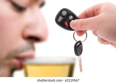 Betrunkenes Fahrkonzept mit einer Hand, die einige Autoschlüssel und einen Mann hält, der Bier im Hintergrund trinkt. Geringe Schärfentiefe.