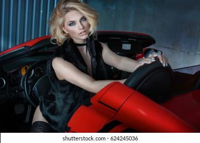 Sexy blonde Frau, die im roten Sportwagen aufwirft.