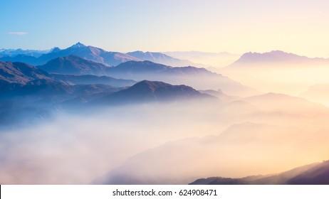 Cordillera con siluetas visibles a través de la colorida niebla matutina.