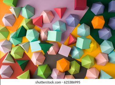 Bunter abstrakter geometrischer Hintergrund mit dreidimensionalen festen Figuren. Rechteckiger Würfel des Pyramiden-Dodekaeder-Prismas, angeordnet auf farbigem Papier.