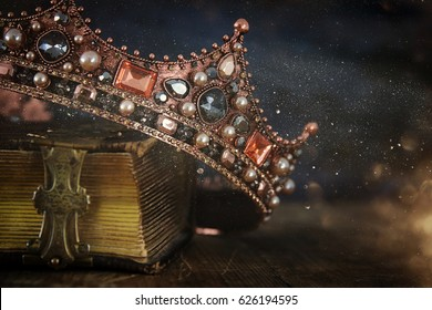 rustig beeld van mooie koningin / koningskroon op oud boek. vintage gefilterd. fantasie middeleeuwse periode
