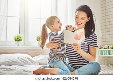 母の日おめでとう!子娘はお母さんを祝福し、はがきを渡します。ママと女の子の笑顔と抱擁。家族の休日と一体感。