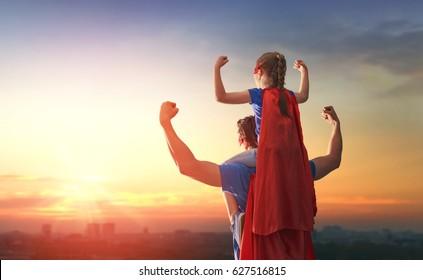 Gelukkig liefdevolle familie. Vader en zijn dochter buiten spelen. Papa en kindmeisje in de kostuums van een superheld. Concept van Vaderdag.