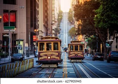 レトロなビンテージスタイルのクロスプロセスフィルター効果、サンフランシスコ、カリフォルニア、米国の日の出の朝の光の中で有名なカリフォルニアストリートに乗って歴史的な伝統的なケーブルカーの古典的なビュー