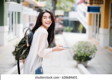Asiatische Frau, die ein Smartphone in der Straße an einem sonnigen Sommertag geht und verwendet