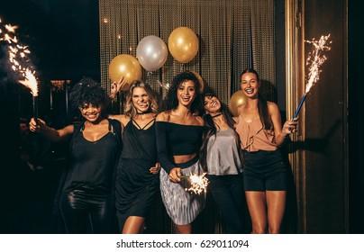 ナイトクラブで大晦日を祝う女の子のグループのショット。線香花火とパブでパーティーをする女性の友人のグループ。
