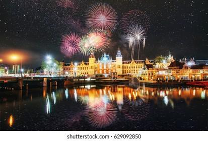 Schöne ruhige Nachtansicht der Stadt Amsterdam. Buntes Feuerwerk auf dem schwarzen Himmelhintergrund. Foto-Grußkarte. Bokeh Lichteffekt, weicher Filter.