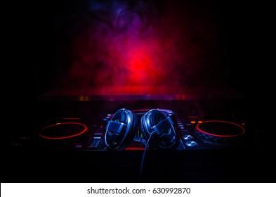 DJ Spinning, Mixing und Scratching in einem Nachtclub, Hands of DJ optimieren verschiedene Track-Steuerelemente auf DJs Deck, Blitzlichter und Nebel, selektiver Fokus, Nahaufnahme