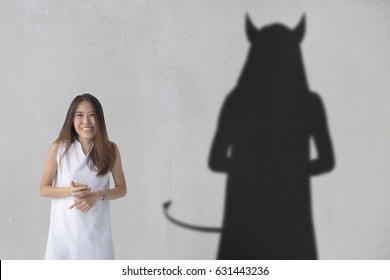 Aziatische vrouw ziet eruit alsof ze een grap aan het uitzetten is terwijl ze een duivelse schaduw heeft.