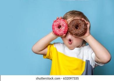 Kleiner glücklicher niedlicher Junge isst Donut auf blauer Hintergrundwand. Kind hat Spaß mit Donut. Leckeres Essen für Kinder. Lustige Zeit zu Hause mit süßem Essen. Kluges Kind.