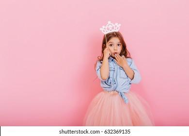 Überraschtes hübsches junges Mädchen im Tüllrock mit Krone auf Kopf, die lokal auf rosa Hintergrund ausdrückt. Erstaunliche süße kleine Prinzessin am Karneval. Platz für Text
