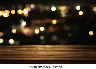 Bild des hölzernen Tisches vor abstraktem unscharfem Restaurant beleuchtet Hintergrund.